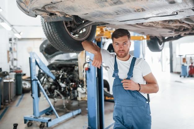 Welkom in onze garage. werknemer in het blauw gekleurde uniform werkt in de autosalon.