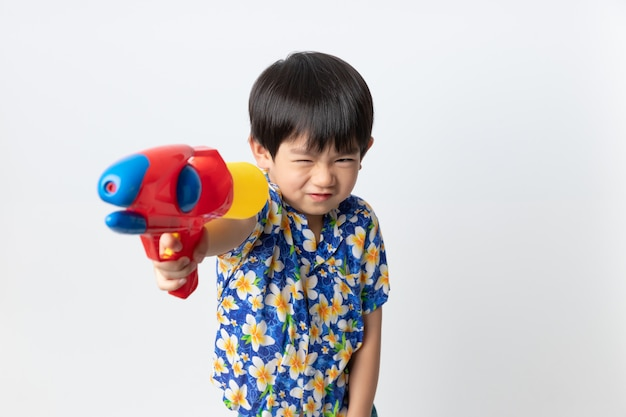 Welkom thailand songkran festival, portret van aziatische jongen draagt bloem shirt glimlachte met water gun automatische waterpistool