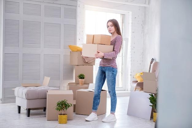 Welkom thuis. mooie donkerharige vrouw die dozen met haar bezittingen naar een nieuw huis draagt, nadat ze onlangs is ingetrokken