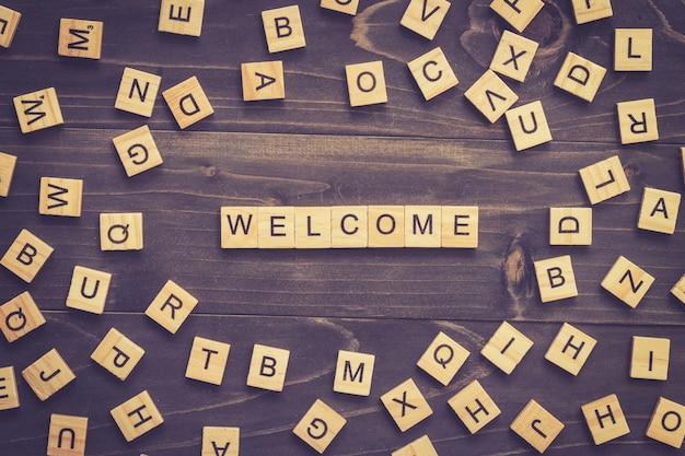 Welkom woord hout blok op tafel voor business concept.