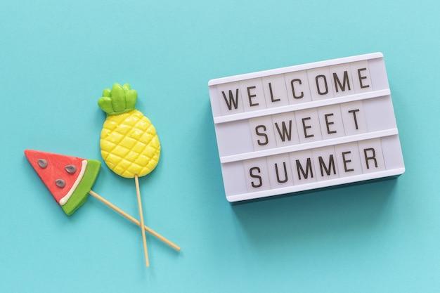 Welkom zoete zomertekst op lichte doos, ananas en watermeloenlollies op stok op blauwe achtergrond