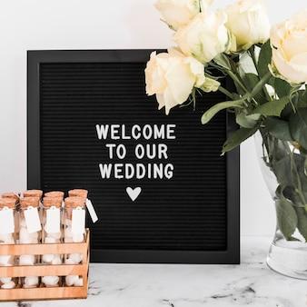 Welkomstbericht voor bruiloft op zwart frame met marshmallow reageerbuisjes en rozenvaas