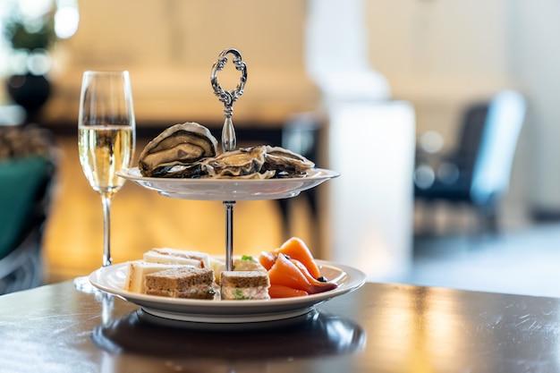 Welkomstcocktail canapes-schotel, verse oester en visgerechten met gerookte zalm en sprankelende champagne.