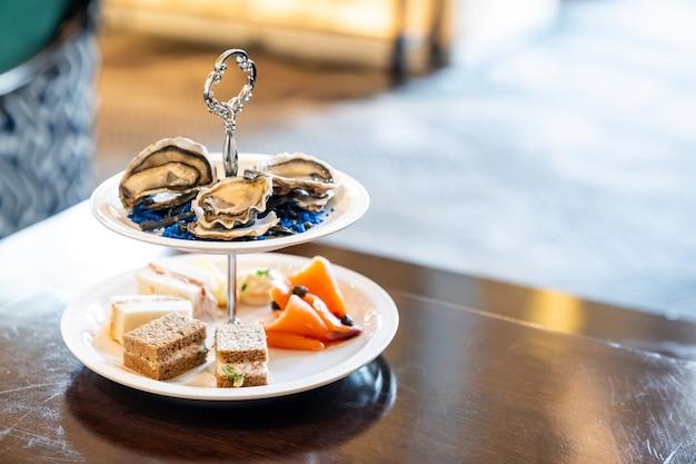 Welkomstcocktail canapes-schotel, verse oester en visgerechten met gerookte zalm.