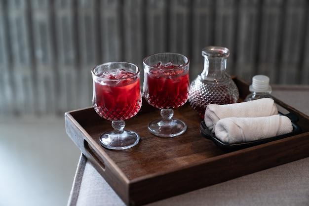Welkomstdrankje rode mocktail en witte handdoek geserveerd op houten dienblad.