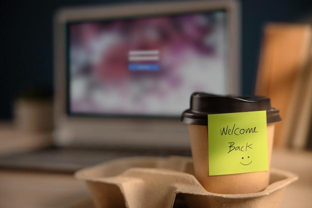 Welkomsttekst over koffiekopje op kantoor