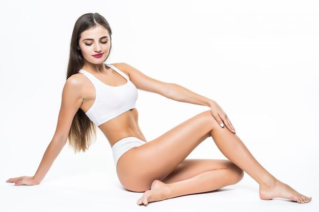 Wellness en beauty concept. mooie slanke vrouw in wit ondergoed zittend op een witte vloer