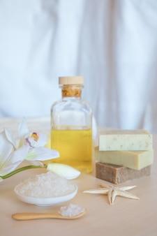 Wellness instelling. zeezout, zeep, handdoek, olie en bloemen op houten achtergrond