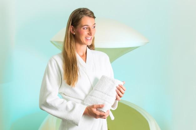 Wellness, jonge vrouw die in kuuroord in tank drijft