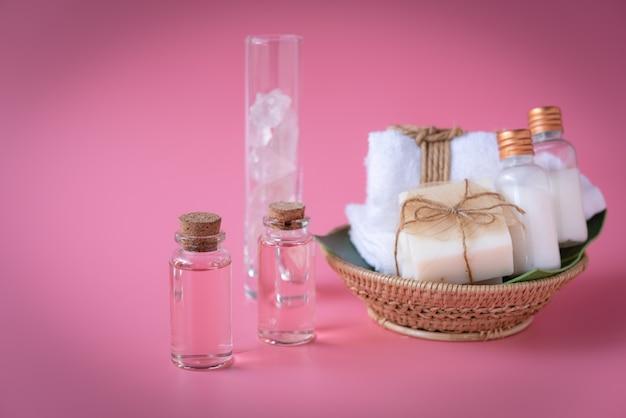 Wellnessconcept van de spa, roze vloeibare fles, melkzeep, witte handdoeken in houten dienblad