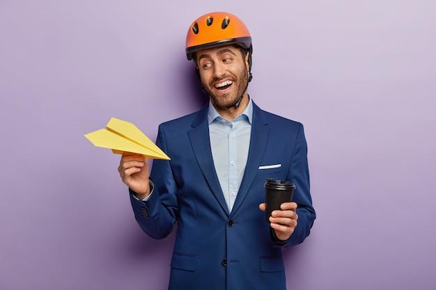 Welvarende gelukkig zakenman poseren in stijlvol pak en rode helm op kantoor
