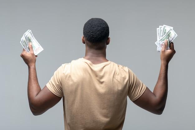 Welzijn. achteraanzicht van sterke donkere huid man met bankbiljetten in opgeheven handen staande tegen een lichte achtergrond