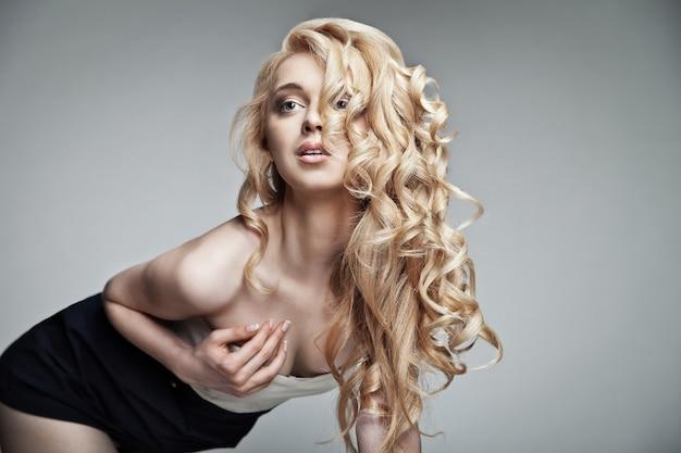 Welzijn en spa. sensueel vrouwenmodel met glanzend krullend lang blond haar. gezondheid, beauty, wellness, haarverzorging, cosmetica en make-up