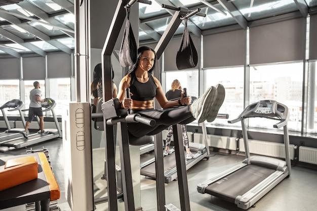 Welzijn. jonge gespierde blanke vrouw oefenen in de sportschool met apparatuur. atletisch vrouwelijk model dat abs-oefeningen doet, haar bovenlichaam, buik opleidt. wellness, gezonde levensstijl, bodybuilding.
