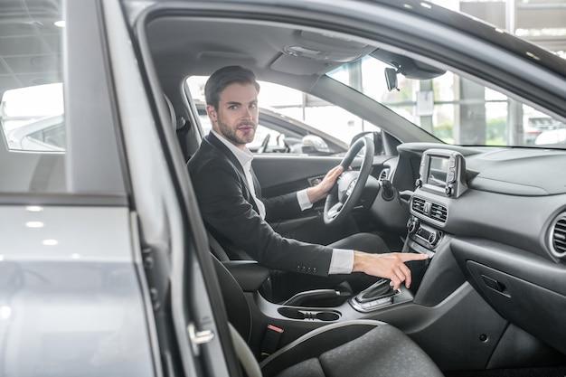 Welzijn. jonge volwassen serieuze man in een donker pak zit in een nieuwe auto die in de winkelsalon rijdt