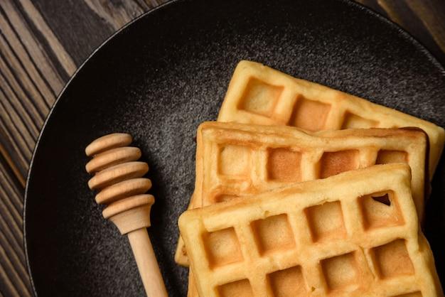 Wenen wafels en houten honing lepel close-up