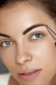 Wenkbrauw correctie. close-up van mooie jonge vrouw met perfecte make-up en lange wimpers wenkbrauwen epileren. portret van sexy vrouwelijk model gezicht en pincet in de buurt van wenkbrauwen. schoonheidsconcept.