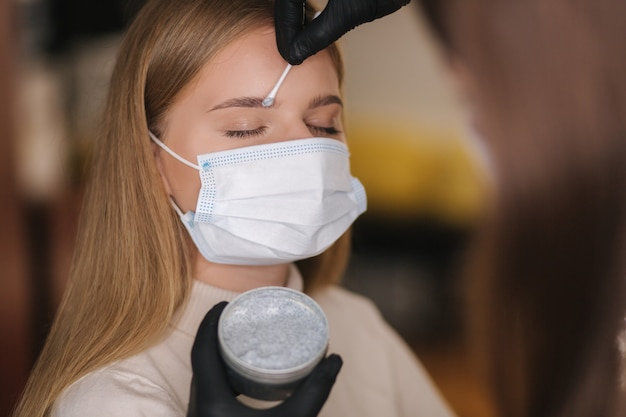 Wenkbrauw- en make-upmeester in beschermend masker geeft vorm om met een pincet uit te trekken