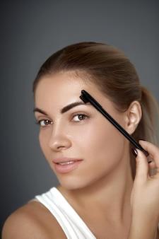 Wenkbrauw make-up. mooie vrouw die wenkbrauwen met kam vormt. detailopname. schoonheidsmeisjesmodel met professionele make-up die wenkbrauwen contouren
