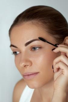 Wenkbrauw make-up. mooie vrouw vormende wenkbrauwen met de close-up van de wenkbrauwborstel
