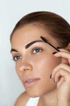 Wenkbrauw make-up. schoonheid model vormende wenkbrauwen met borstel wenkbrauw close-up