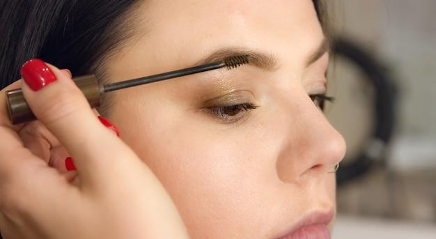 Wenkbrauw make-up. visagist schildert met een borstel de wenkbrauw.