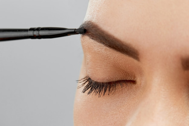 Wenkbrauwcorrectie. close-up van mooie jonge vrouw met perfecte make-up en lange wimpers wenkbrauwen plukken.