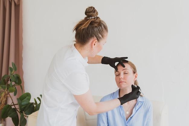 Wenkbrauwmeester schoonheidsspecialiste modelleert de wenkbrauwen van een jonge vrouw