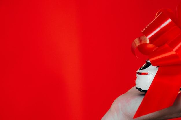 Wenselijk cadeau op kerstconcept. close-up foto van kleine speelgoed luxe stijlvolle auto omwikkeld met rood lint geïsoleerd over kleur rode achtergrond op een vrouwelijke hand 23 augustus 2021 in ryazan, rusland