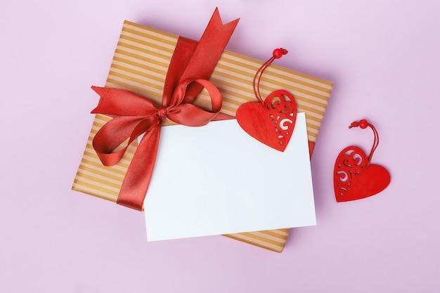 Wenskaart, cadeau en harten op een roze tafel. valentijnsdag