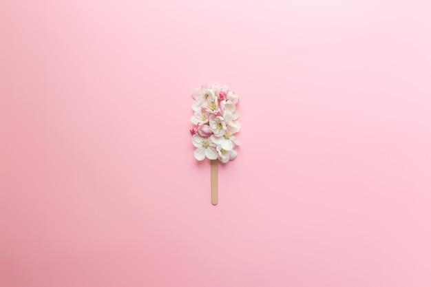 Wenskaart concept plat lag op roze achtergrond met appelbloesem ijs lolly op een stokje. hoge kwaliteit foto