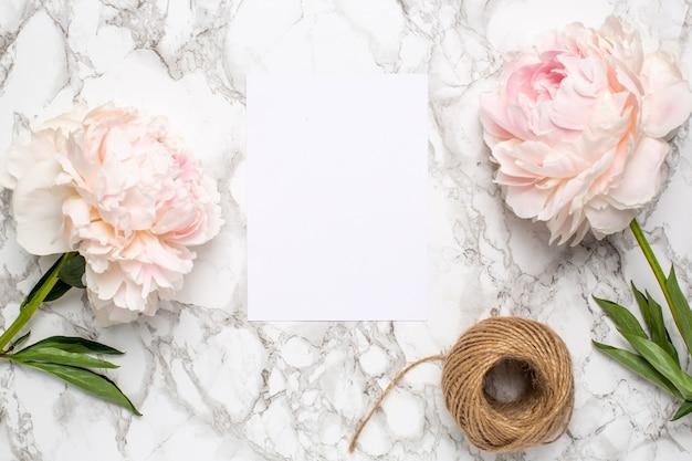 Wenskaart en roze bloemen pioen op een op een marmeren oppervlak. vakantie- en zomeritem.