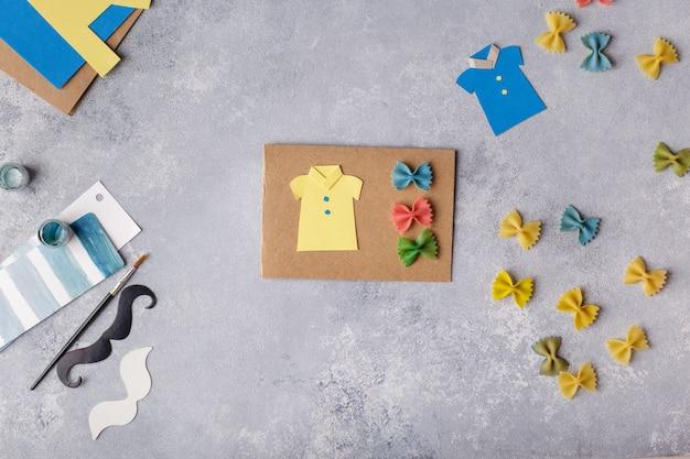 Wenskaart maken voor vaderdag. shirt met vlinder van pasta. kaart van papier. snor