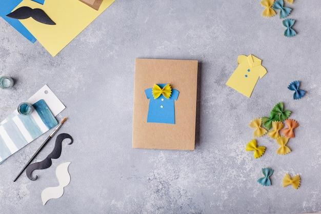 Wenskaart maken voor vaderdag. shirt met vlinder van pasta. kunstproject voor kinderen.