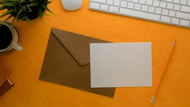 Wenskaart met bruine envelop op creatieve werktafel met computertoetsenbord en decoraties