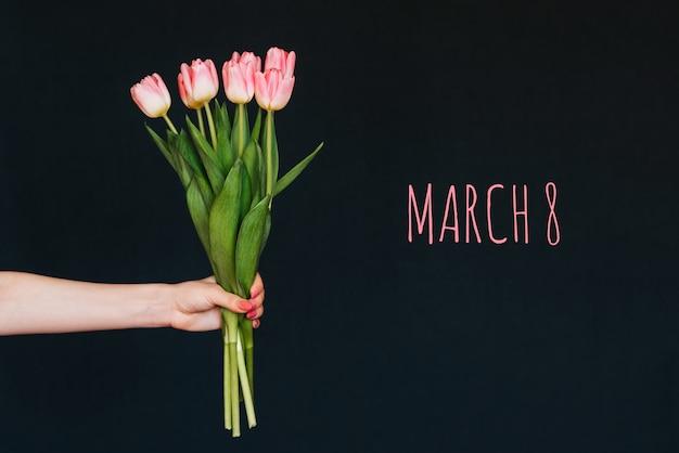 Wenskaart met de inscriptie 8 maart. boeket van roze bloemen van tulpen