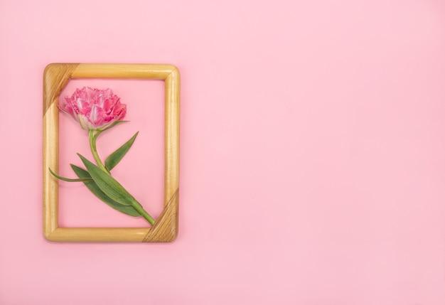 Wenskaart met een badstof tulp in een houten frame op een roze achtergrond voor de vakantie valentijnsdag of moederdag en pasen
