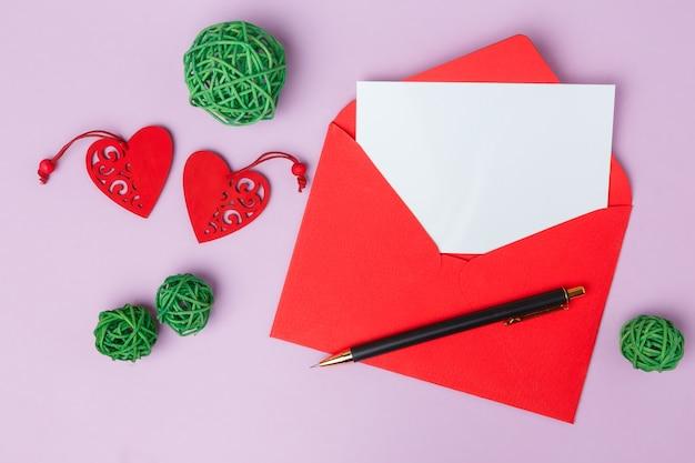 Wenskaart met een envelop en hartjes op een roze tafel. valentijnsdag