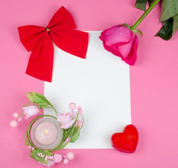 Wenskaart met een roos, een rode strik, een hart en een kaars