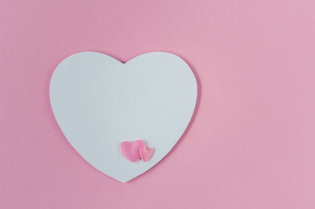 Wenskaart met een roze en witte harten op een roze