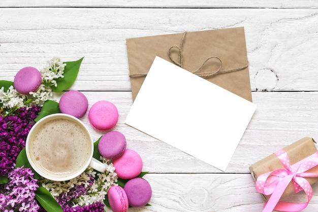 Wenskaart met lente lila bloemen, kopje cappuccino en geschenkdoos