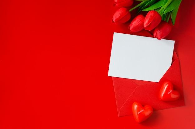 Wenskaart met liefde. rode envelop met blanco papier, boeket tulpen en hartvormige kaarsen.