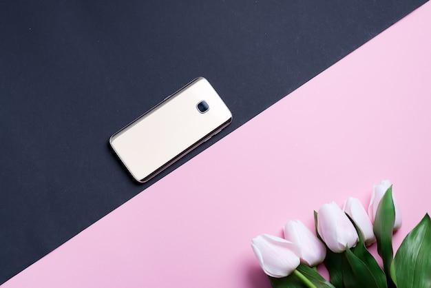 Wenskaart met mobiele telefoon en lente roze tulpen bloem op een duotoon diagonale achtergrond.