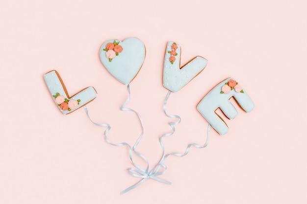 Wenskaart met word love van zelfgemaakte koekjes als ballonnen verbonden door lint. valentijnsdag vakantie