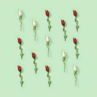 Wenskaart regelmatig creatief patroon van natuurlijke droge rode bloem eustoma op zacht groen. bloemdessin