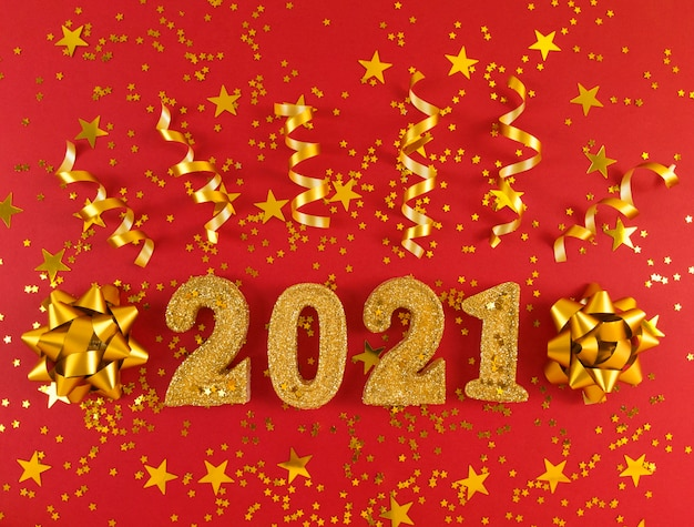 Wenskaart van het nieuwe jaar 2021. gouden glinsterende figuren, sterren, strikken en linten op rode achtergrond.