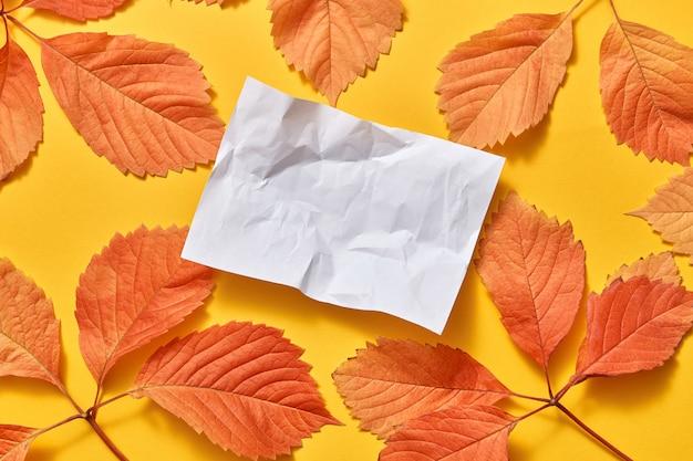 Wenskaart van verfrommeld vel papier met gekleurde herfstbladeren op een gele achtergrond, kopieer ruimte. plat leggen.