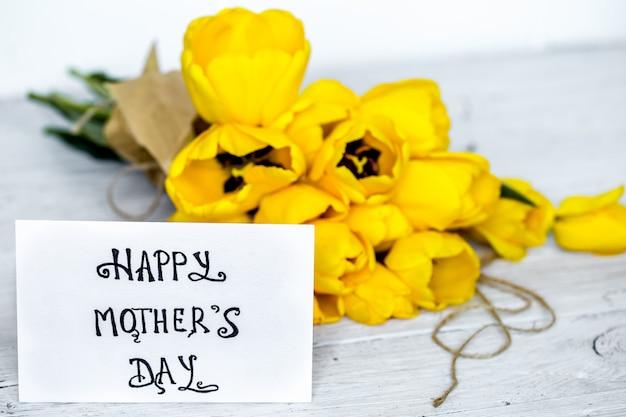 Wenskaart voor moederdag en gele tulpen op houten tafel