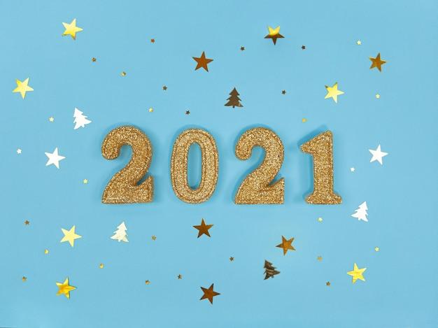 Wenskaart voor nieuwjaar 2021. gouden glinsterende figuren en confetti op een blauwe achtergrond.