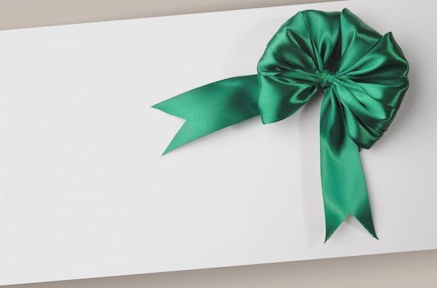 Wenskaartsjabloon met groene strik met witte lege kopie ruimte